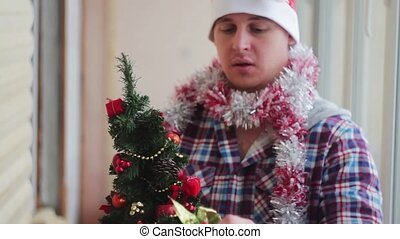 man dresses beautiful little glowing Christmas tree