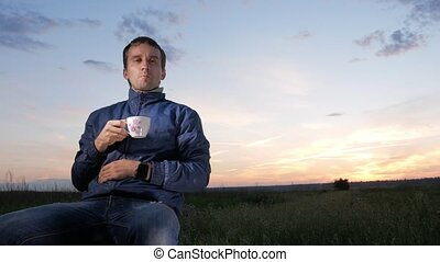 A young man drinks a hot drink from a mug at sunset. Beautiful sky behind.