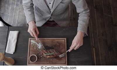 a young man eating a steak