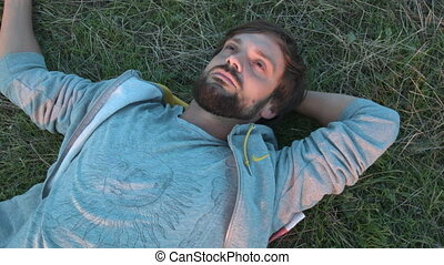A young man enjoys the nature of lying on the ground