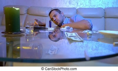 a young man experiences hallucinations from taking drugs and alcohol while lying on the floor next to a table in the living room