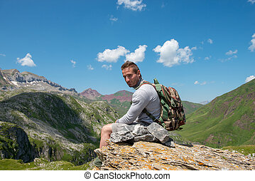 young man hiker sitting on a rock in mountain