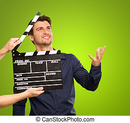 A Young Man Holding A Clapboard And Acting On White...