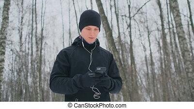 A young man in a black hammer in the winter is preparing to...