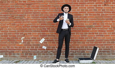A young man in a black suit and hat counts money dollars on brick wall background, slow motion, style