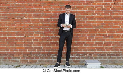 A young man in a black suit counts money against the background of a kipic wall and puts half of himself in his pocket, theft, an intermediary, slo-mo