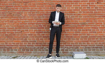 A young man in a black suit counts money against the background of a kipic wall and puts half of himself in his pocket, theft, an intermediary, slo-mo, caucasin