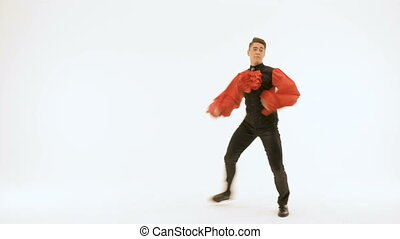 A young man in a black suit is dancing on a white background. Beautifully doing ballet exercises