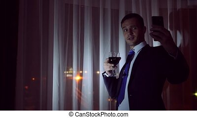 A young man in a business suit drinks alcohol, and makes selfie on his smartphone, stands at the window of the house at night. Window panorama, view of the city, night lights.