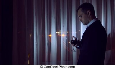 A young man in a business suit is drinking alcohol, standing at the window of a house at night. Window panorama, view of the city, night lights. 4k