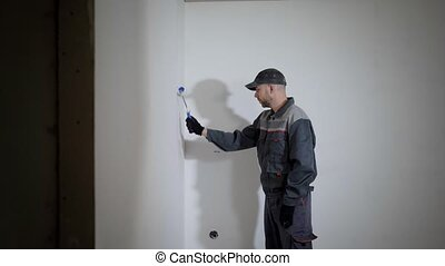 a young man in a construction uniform paints the walls in...