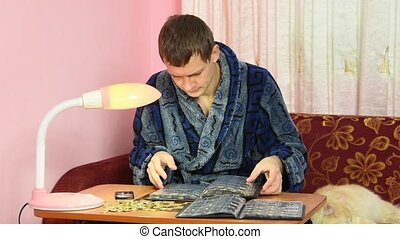 A young man in a dressing gown watching his collection of...