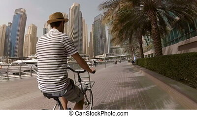 A young man in a hat, striped t-shirt and shorts riding his bike on the promenade among the skyscrapers and yachts in Dubai Marina, UAE