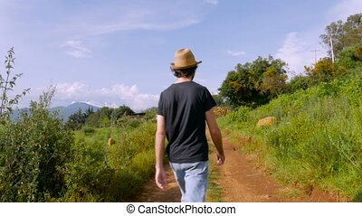 A young man in a hat walks on dirt road and sits to look at the view