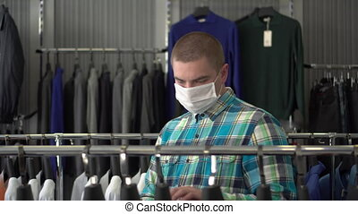 A young man in a medical mask is choosing clothes in a store. Clothing store.