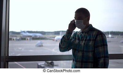 A young man in a medical mask talks on the phone against the background of a window at the airport. Airplanes in the background.