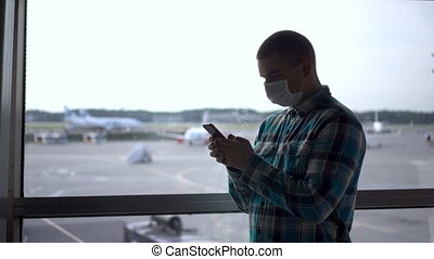 A young man in a medical mask with a phone in his hands against the background of a window at the airport.