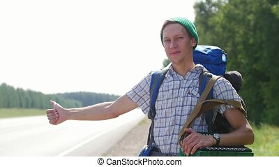 A young man in a plaid shirt, a green hat and a backpack...