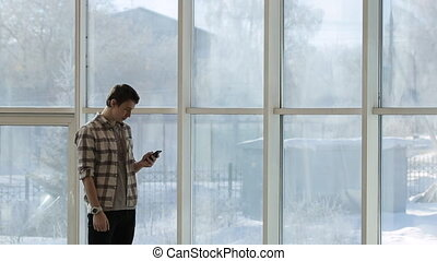 A young man in a plaid shirt and a clock on hand, looking at smartphone screen, standing beside a panoramic window with a winter landscape.
