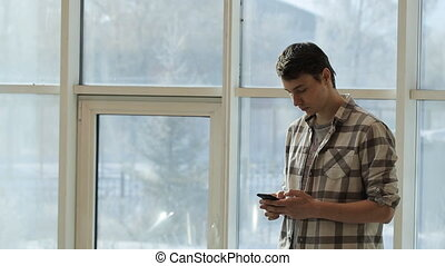 A young man in a plaid shirt stands in front of panoramic windows and keep smartphone in hand.
