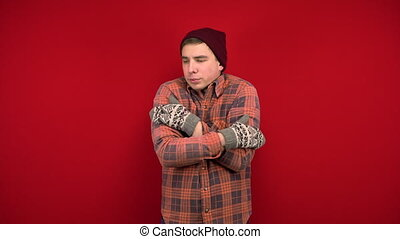 A young man in a red shirt, hat and mittens is cold and hugs himself to keep warm. Shooting in the studio on a red background. 4k