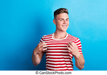 A young man in a studio, wearing striped red and white T-shirt.