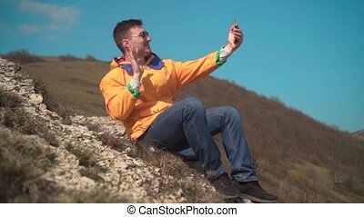 A young man in a yellow jacket, blue jeans and glasses sits in the mountains, enjoys the scenery, talking on video.