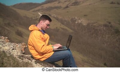 A young man in a yellow jacket, blue jeans and glasses sits in the mountains, opens the laptop and starts working.