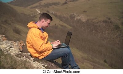 A young man in a yellow jacket, blue jeans and glasses sits in the mountains, works for a laptop, is nervous, swears.