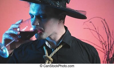 a young man in a zombie costume for halloween, with a glass of wine in his hands. 4k, slow motion. close-up