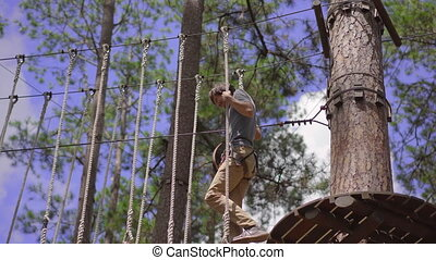 A young man in an adventure park. He wears a safety harness. He climbs on a high rope trail. Outdoor amusement center with climbing activities consisting of zip lines and all sorts of obstacles.