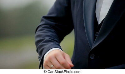 A young man in black suit adjusts his cufflinks of white shirt. Indoor. Close-up. Interior. Sunshine. Steady