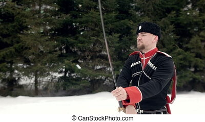 A young man in Cossack clothes swinging a sword in a winter...