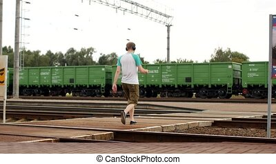 A young man in headphones crosses the railway tracks and listens to music, does not hear the approaching train
