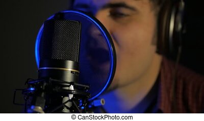 A young man in headphones sings a song near a microphone in a recording studio under natural light. 4k