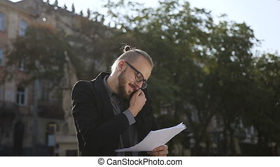 A young man in his glasses holds documents in his hand