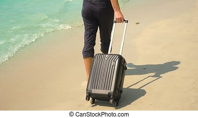 A young man in pants and a classic shirt with a suitcase walks along the beach against the backdrop of the turquoise sea. freelance concept, rest