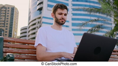 A young man in the summer of palm trees sitting with a laptop and typing on the keyboard