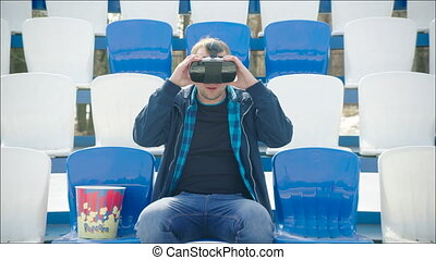 A young man in VR glasses at the stadium