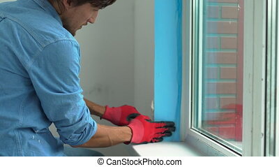 a young man installing plastic window. Installer fills the...