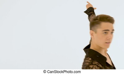 A young man is dancing against a white wall. close-up