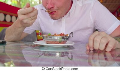 A young man is eating an Indian meat dish in a tropical cafe...