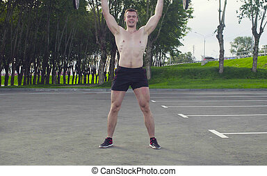 A young man is lifting barbell