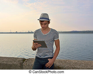 A young man is looking on a tablet