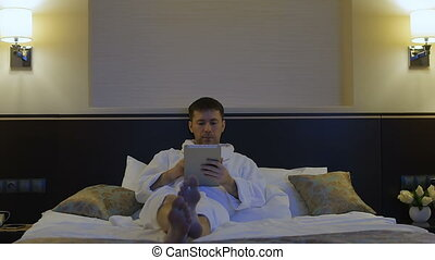 A young man is lying on a bed in a hotel and looks into the phone, tablet