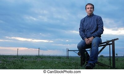 A young man is sitting and looking at the camera at sunset. A field of green grass behind. Beautiful sky.