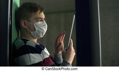 A young man is sitting at home in quarantine with a tablet ...
