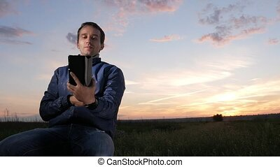 A young man is sitting at sunset and talking on a video call on a tablet. Beautiful sky behind.