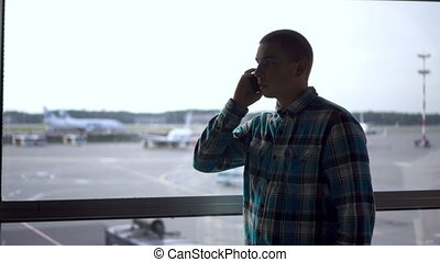 A young man is talking on the phone against the background of a window at the airport. Airplanes in the background.