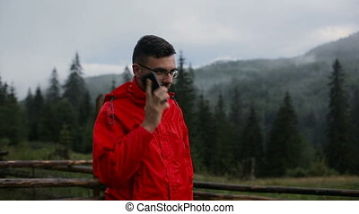 A young man is talking on the phone in the evening in the mountains. Around the forest in the fog